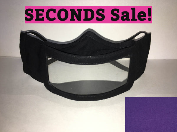 "A black cotton face mask featuring a plastic window over the mouth to help the wearer communicate with people who rely on reading lips. A pink rectangle with the words ""seconds sale!"" is above the mask. A purple rectangle is in the bottom right corner."