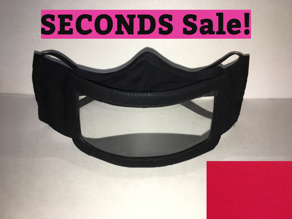 "A black cotton face mask featuring a plastic window over the mouth to help the wearer communicate with people who rely on reading lips. A pink rectangle with the words ""seconds sale!"" is above the mask. A red rectangle is in the bottom right corner."