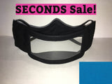 "A black cotton face mask featuring a plastic window over the mouth to help the wearer communicate with people who rely on reading lips. A pink rectangle with the words ""seconds sale!"" is above the mask. A turquoise rectangle is in the bottom right corner."