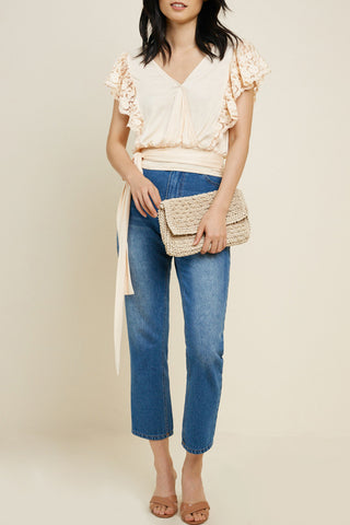CREAM KNIT CRISS-CROSS FRONT TOP WITH LACE SHOULDER DETAIL. ELASTIC SMOCKED WAIST WITH TIE BACK.