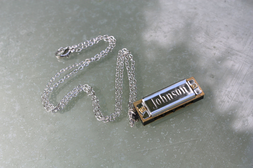 "Johnson ""Blues King"" working miniature harmonica on a neck chain."