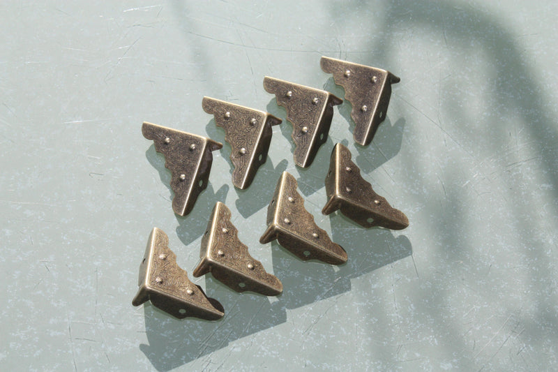 Small dotted antiqued bronze corner protectors with embossed design, fixing nails included.