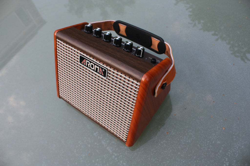 Aroma AG-15 rechargeable battery acoustic guitar amp. 15W output, woodgrain cabinet with tweed fretcloth and carry strap.