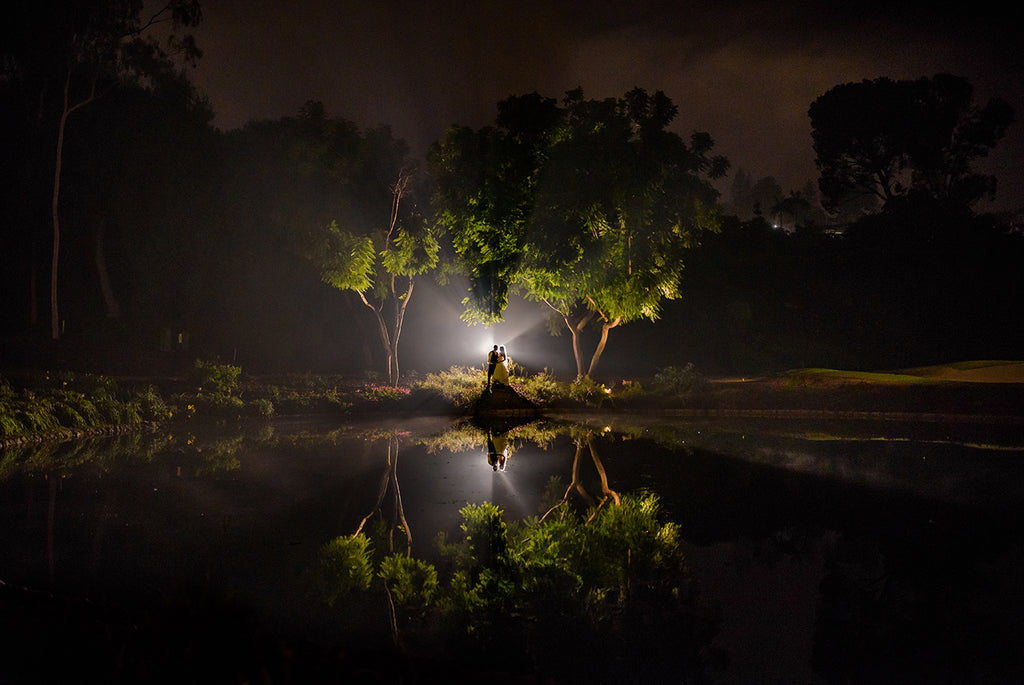 Adrian Ong image of bride and groom at night backlit trees reflection in pond