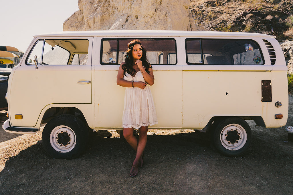 Adrian Ong image of girl in short white dress in front of cream colored vintage Volkswagen VW bus at the beach