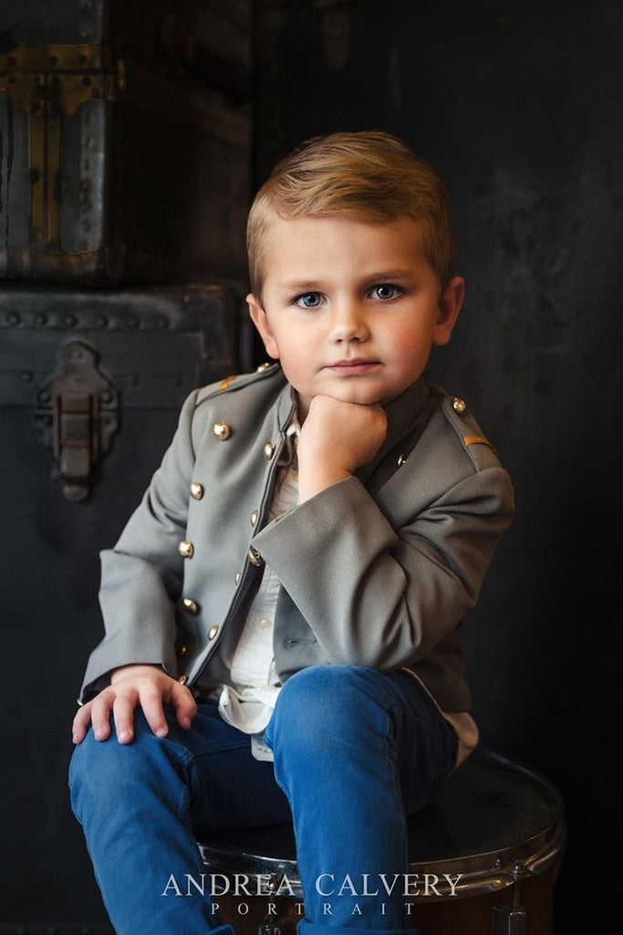 Andrea Calvery portrait of little boy with jeans and grey jacket chin resting on hand