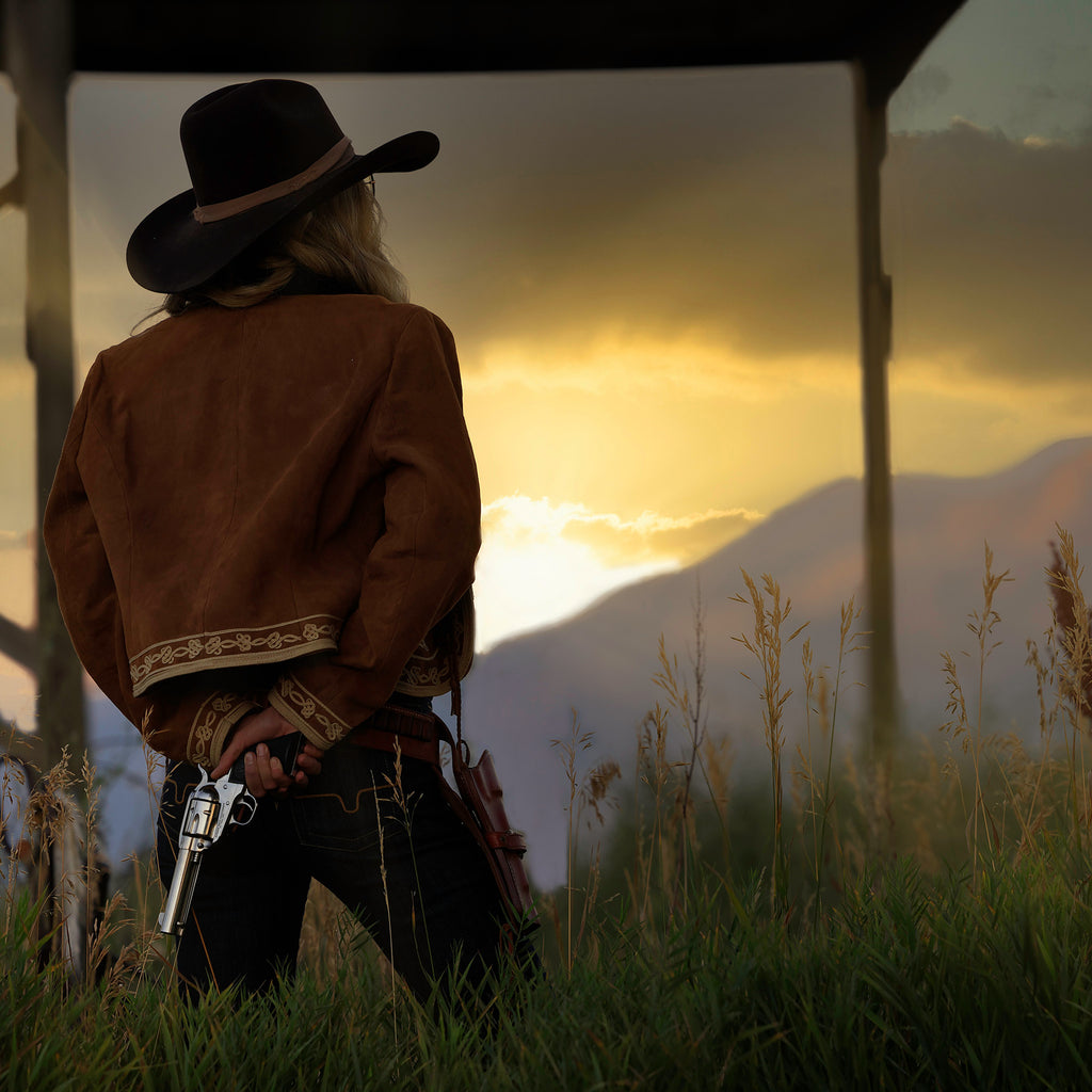Bruce Dorn model wearing cowboy hat standing at sunset with six shooter gun behind back