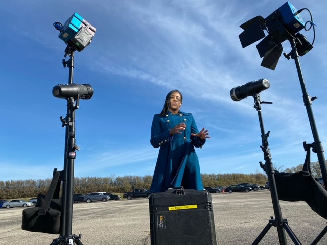 Carmaine Means woman journalist in blue jacket with lights and camera in foreground