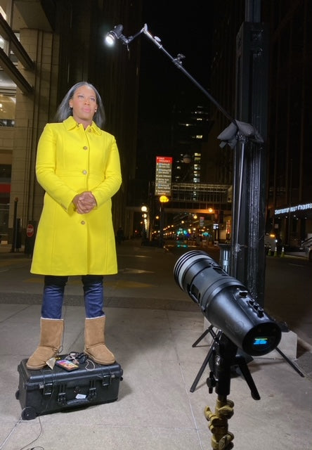 Carmaine Means woman journalist in yellow jacket at night