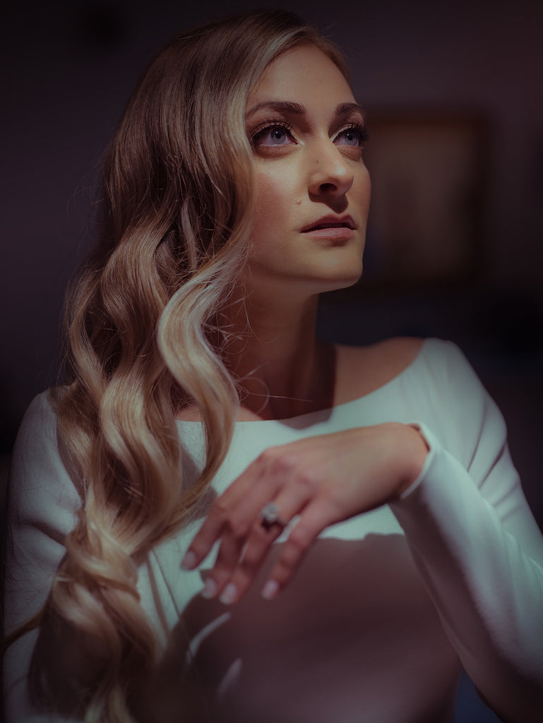 Charles Maring portrait of woman with blue eyes blond wavy hair wearing white boatneck top dramatic lighting diamond ring