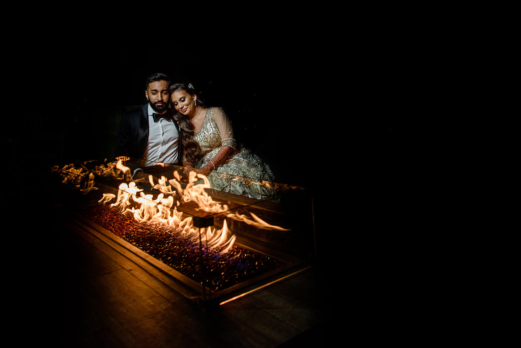Erum Rizvi portrait of bride and groom sitting by firepit