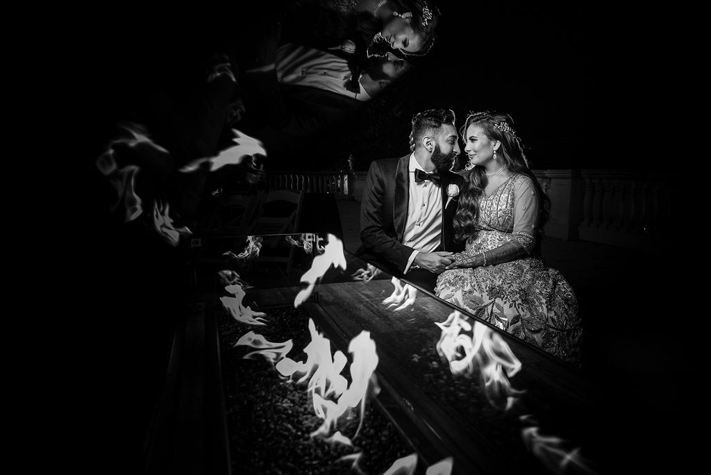 Erum Rizvi portrait of bride and groom sitting by firepit with reflection in glass black and white