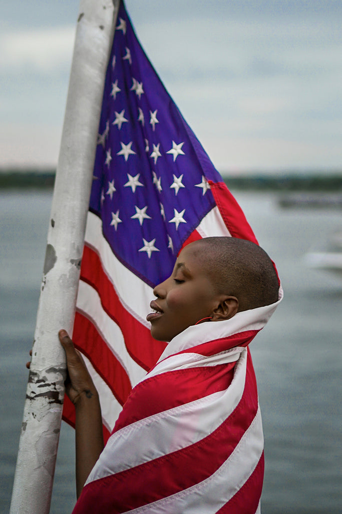 Eyenamics Photograph of African American woman wrapped in American Flag near lake