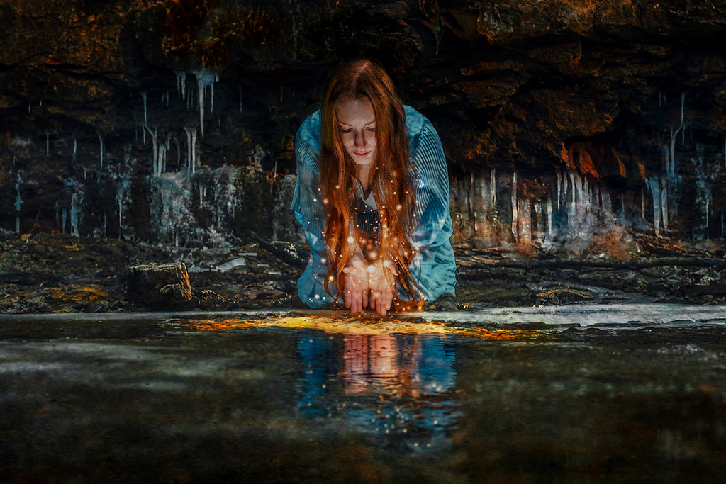 Eyenamics photograph of red head woman wearing blue dress in cavern with icicles sparkles on water