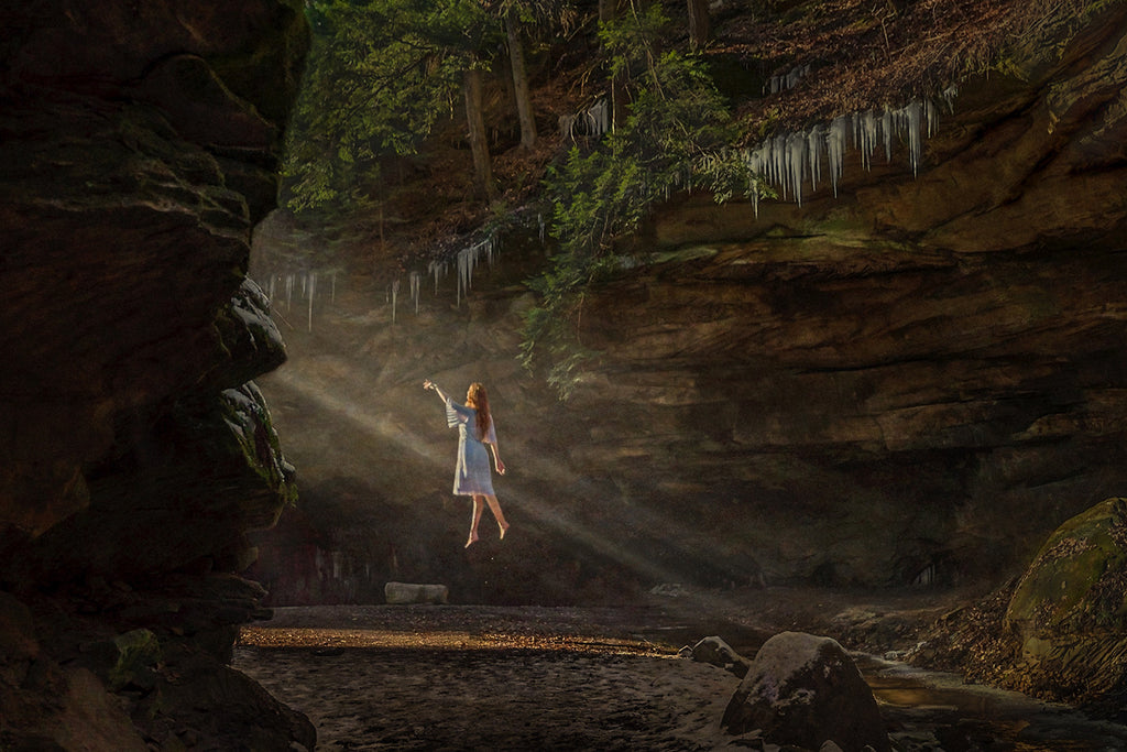 Eyenamics photograph of woman floating up to ray of light in forest