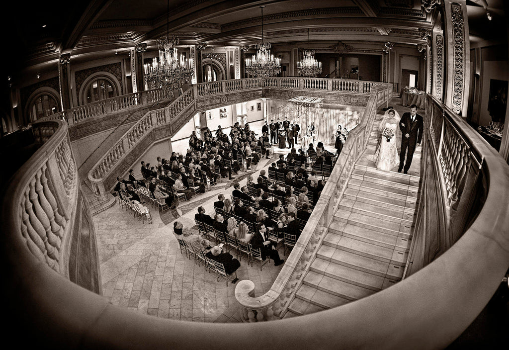 Greg Gibson wide angle bride and father walking down staircase with view of ceremony
