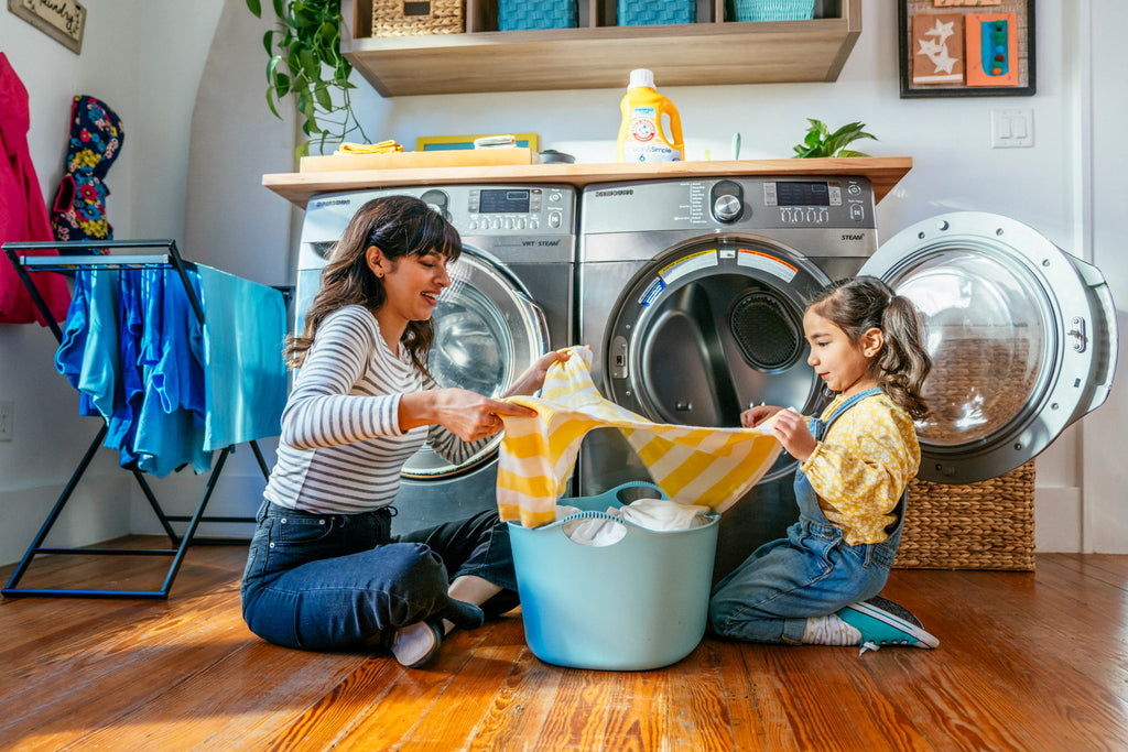 Inti StClair-Mom-daughter-folding-laundry-together-on-floor-by-dryer-arm-hammer-lifestyle-Inti-St-is20191217_AH_1896