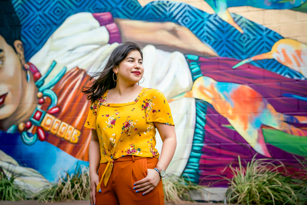 Inti StClair-Portrait-profile-latina-woman-in-floral-yellow-top-in-front-of-brightly-colored-Frida-Kahlo-mural-Inti-St-Clair-is20190409_StEds_10426