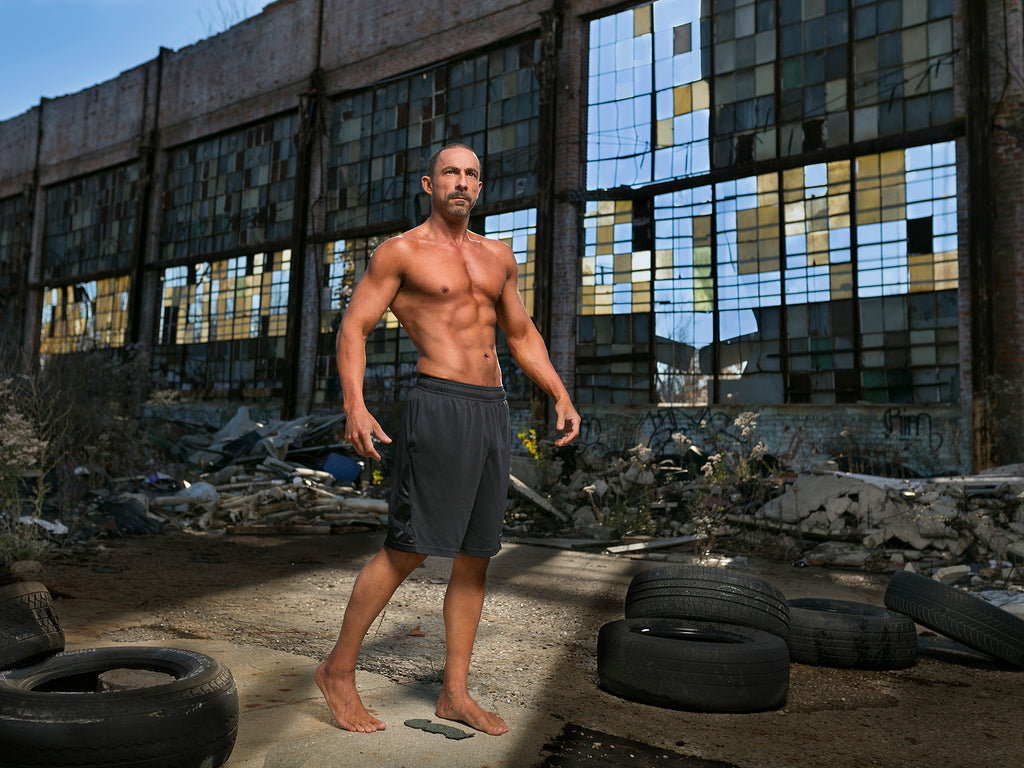 James Schmelzer Atheletic man wearing shorts in old tire yard