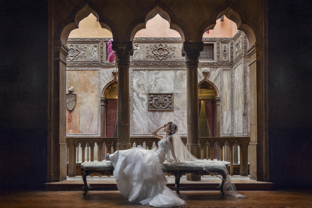Jeremy Chan bridal portrait bride laying on fancy bench in decorative room