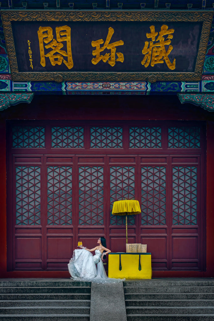 Jeremy Chan bride in wedding dress sitting at yellow cart on stairs holding yellow box yellow parasol