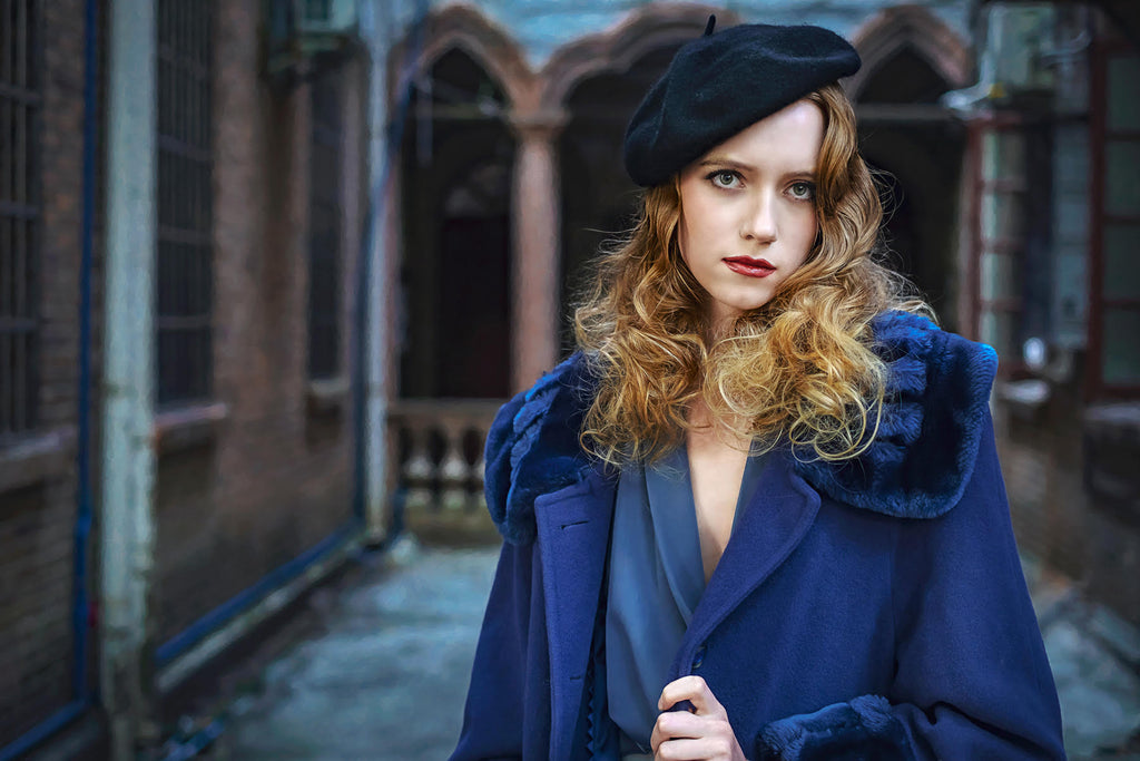 Jeremy Chan portrait of red headed woman wearing blue jacket and dress and black beret pouty expression
