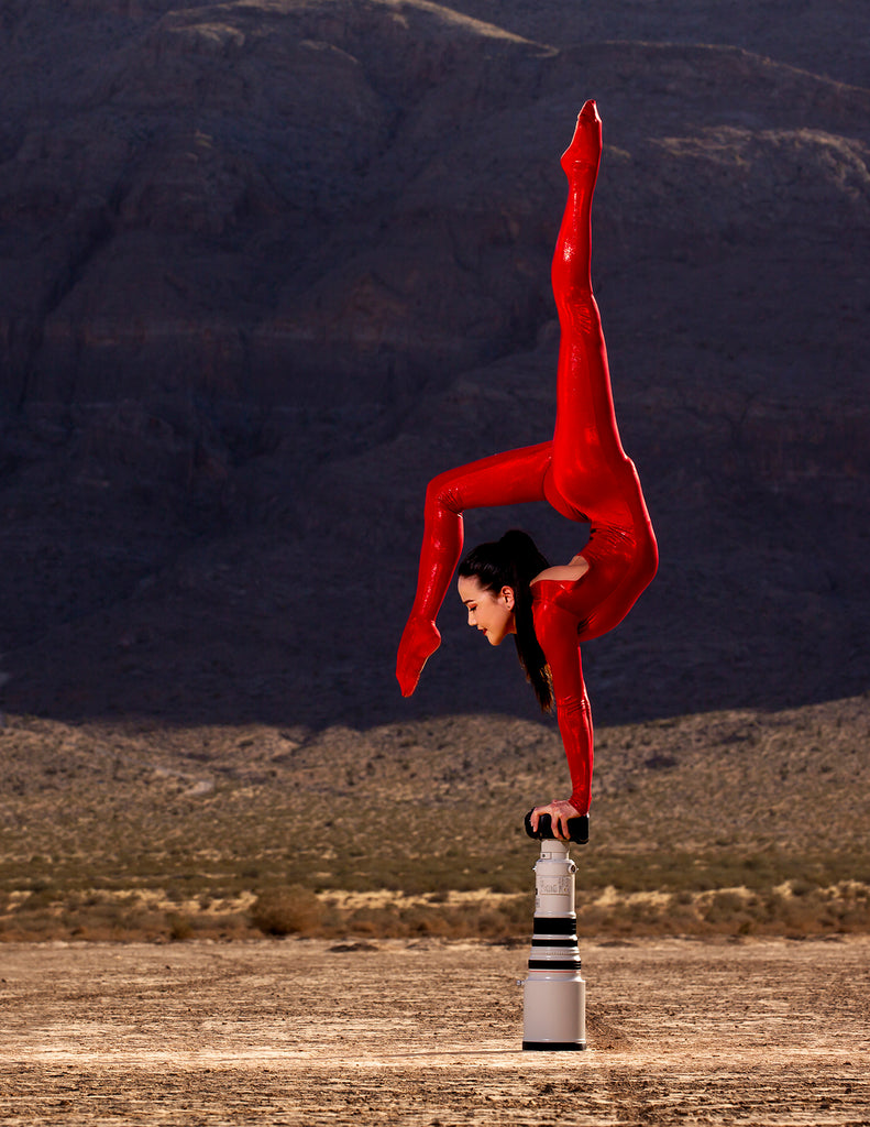 Jerome Hamilton contortionist in red leotard hand balancing on large lens