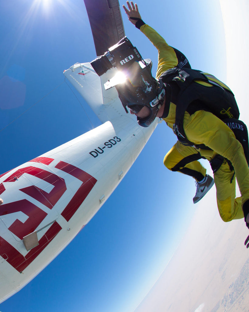 Joe Jennings image of man in yellow skydiving white airplane with red lettering in background
