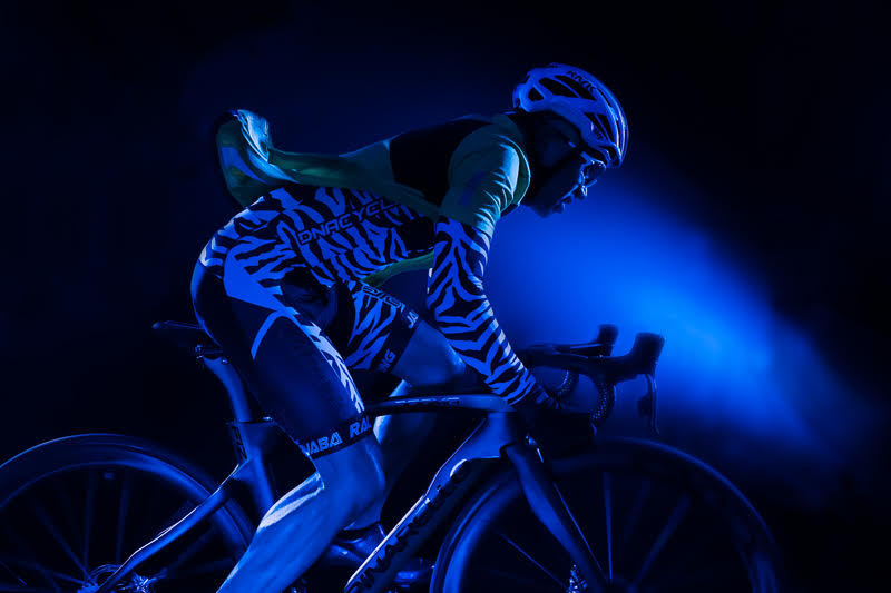 John Deven image of man wearing zebra bike shirt on bicycle blue background