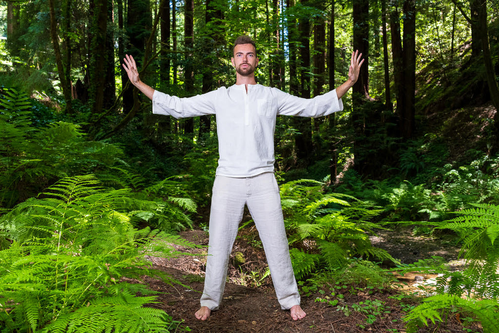 John Deven portrait of man in white exercising chi gong tai chi green ferns in redwood forest