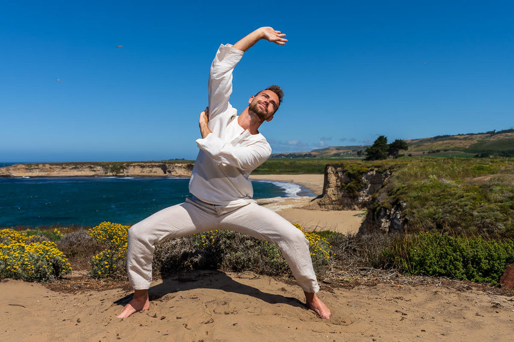 John Deven portrait of man wearing white practing tai chi excercising chi gong at the beach on a cliff