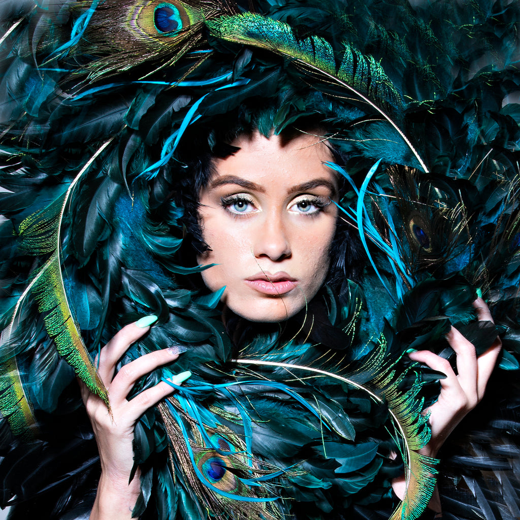 Keith Cephus portrait of woman face surrounded by peacock feathers