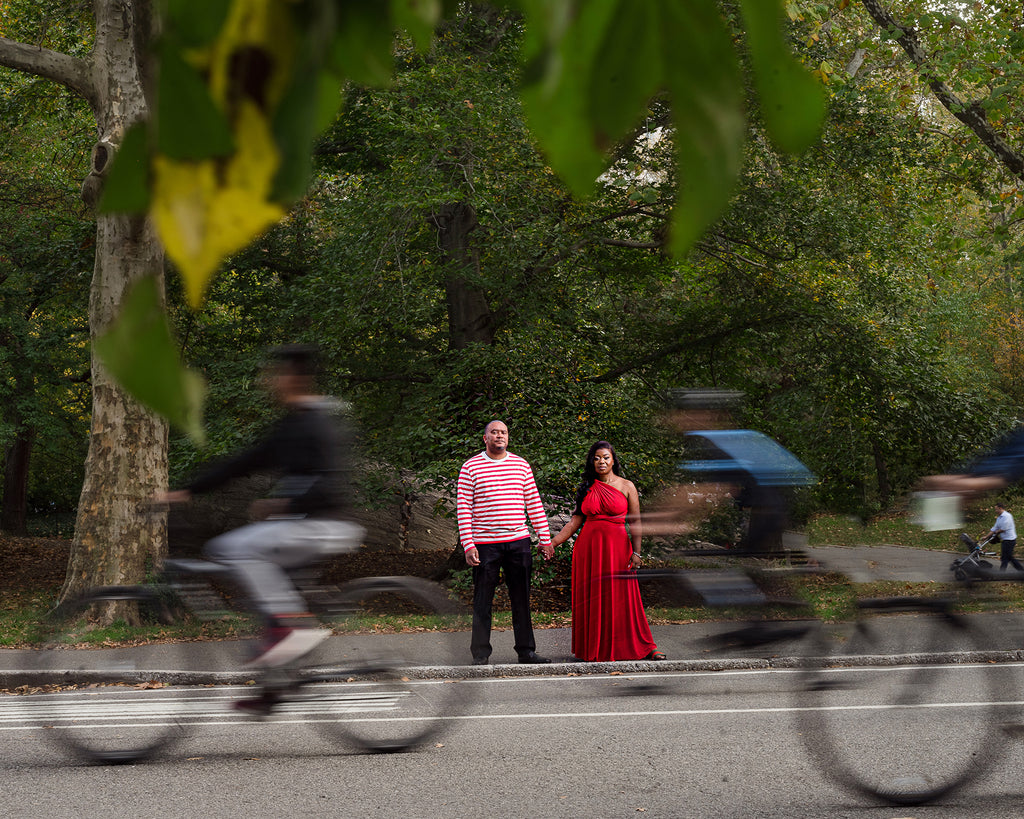 Kesha Lambert portrait of man in pink shirt and woman in red dress bicycles zooming past