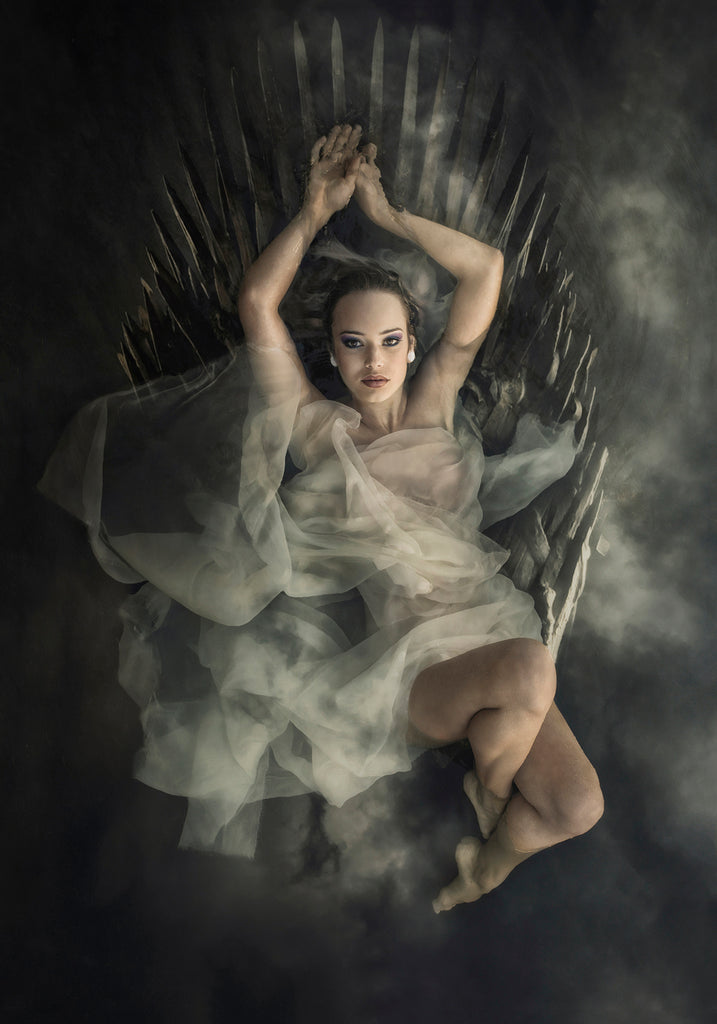 Kristi Elias Photograph of woman in white tule laying in spiky wood chair