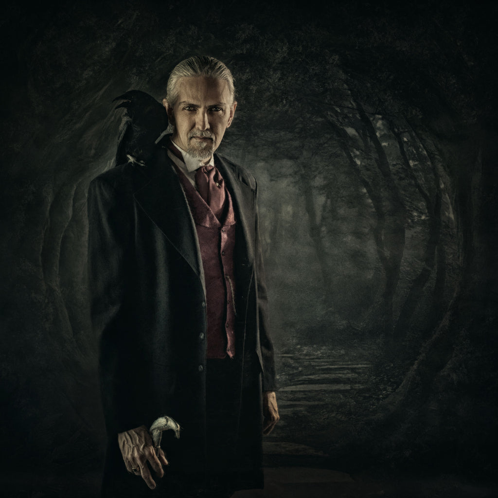 Kristi Elias photograph of man with crow on shoulder raven on shoulder in a dark forest man wearing suit