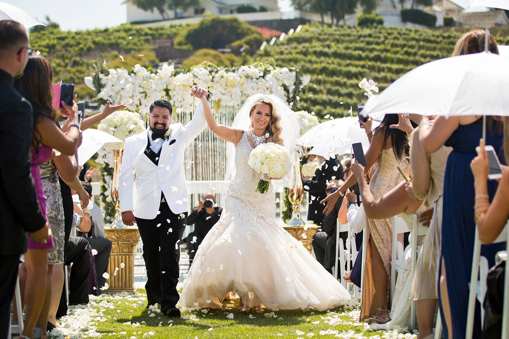 Manuel Ortega bride and groom walking down the aisle holding hands raised up with vineyard in background rose petals flying