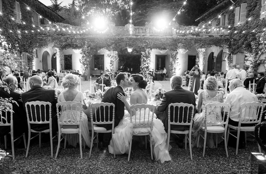 Marcus_Bell_Bride and Groom kissing at head table during reception with guests