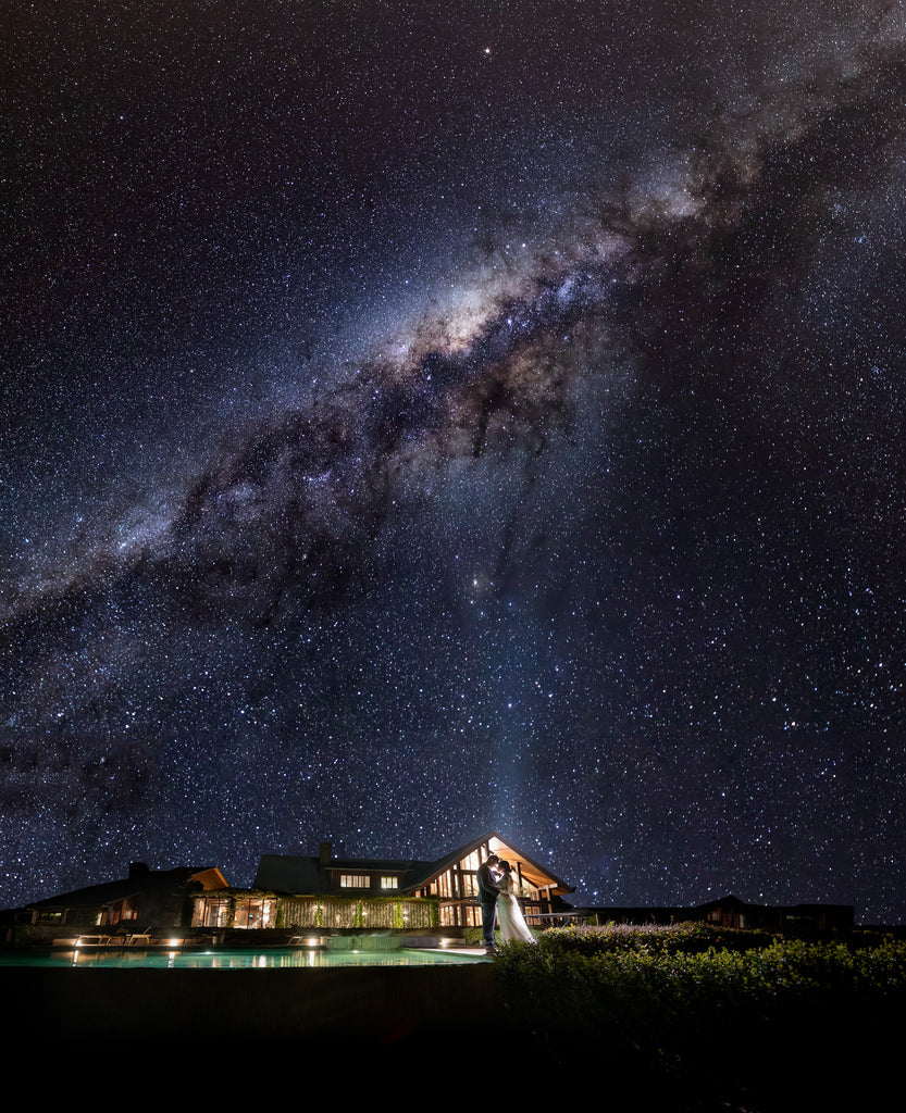 Marcus_Bell_Bride and Groom outside with lodge in background and Milky Way stars in sky