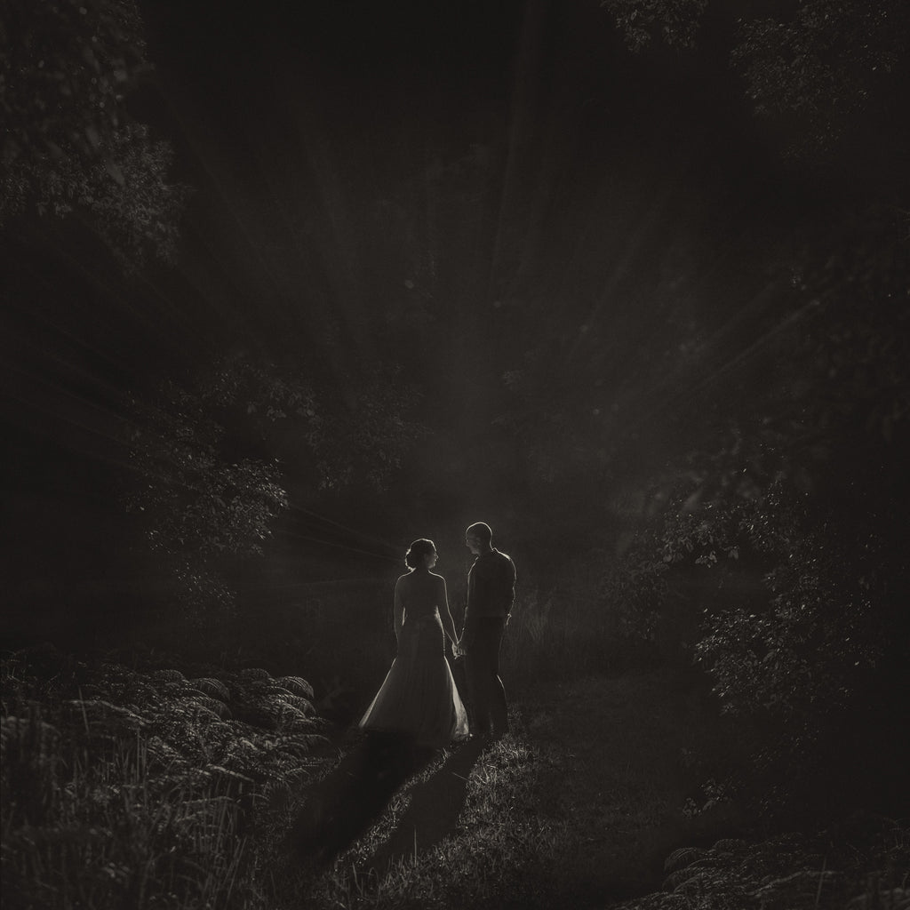 Marcus_Bell_bride and Groom walking in fern forest with trees black and white