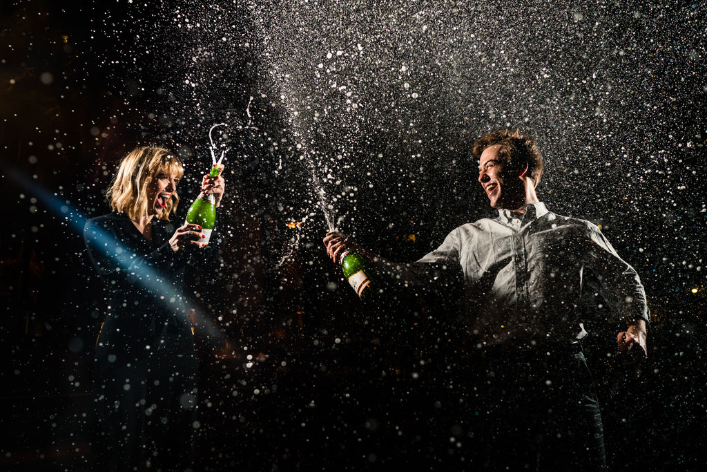 Megan Allen image of man and woman bride and groom spraying champagne celebrating