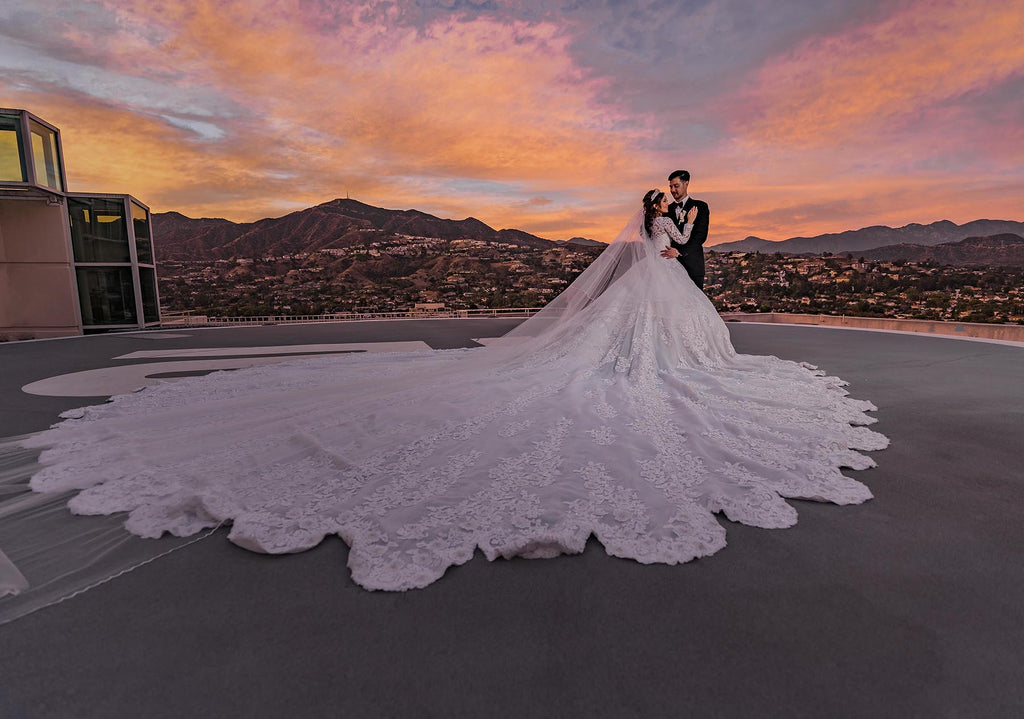 Ning Wong portrait of bride and groom on rooftop at sunset with landscape and large bridal train
