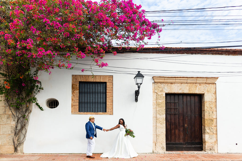 Petronella Lugemwa bride and groom holding hands bouquet in front of old historic building and bougainvillea