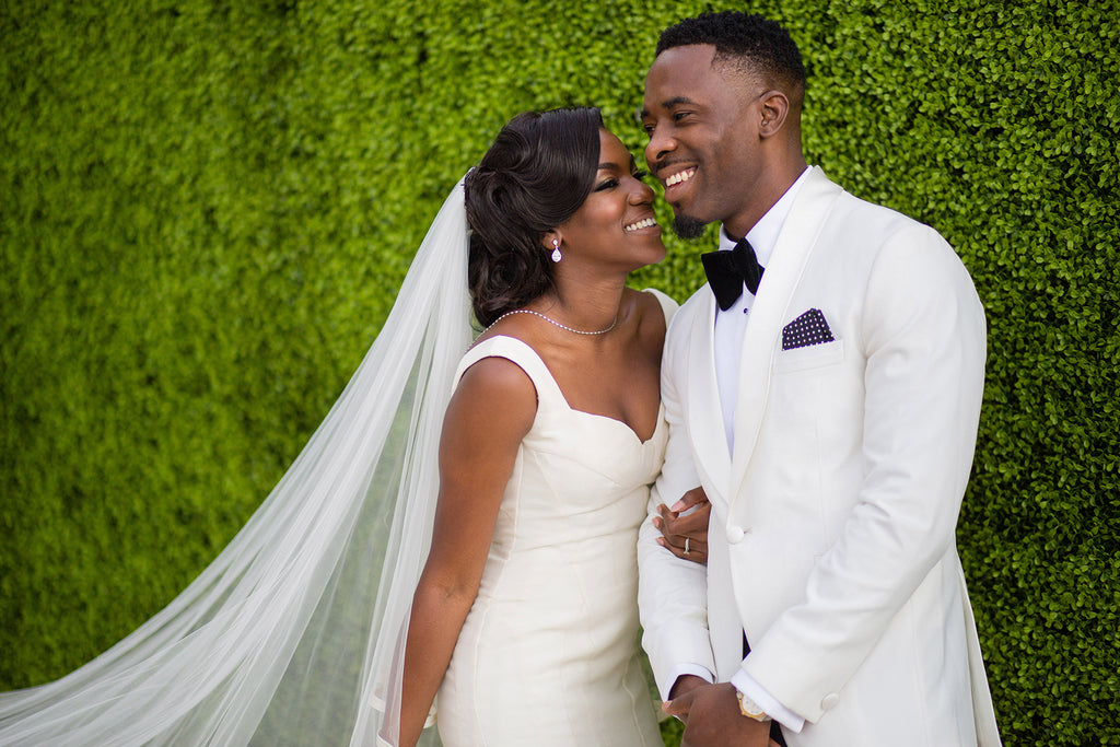 Petronella Lugemwa bride and groom in white background green lush bushes
