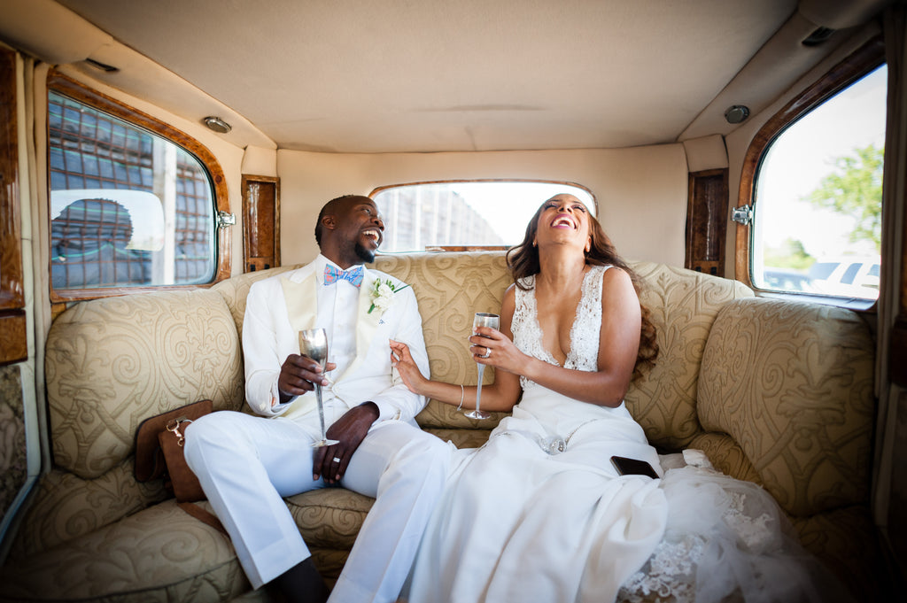 Petronella Lugemwa bride and groom sitting inside vintage car laughing drinking champagne