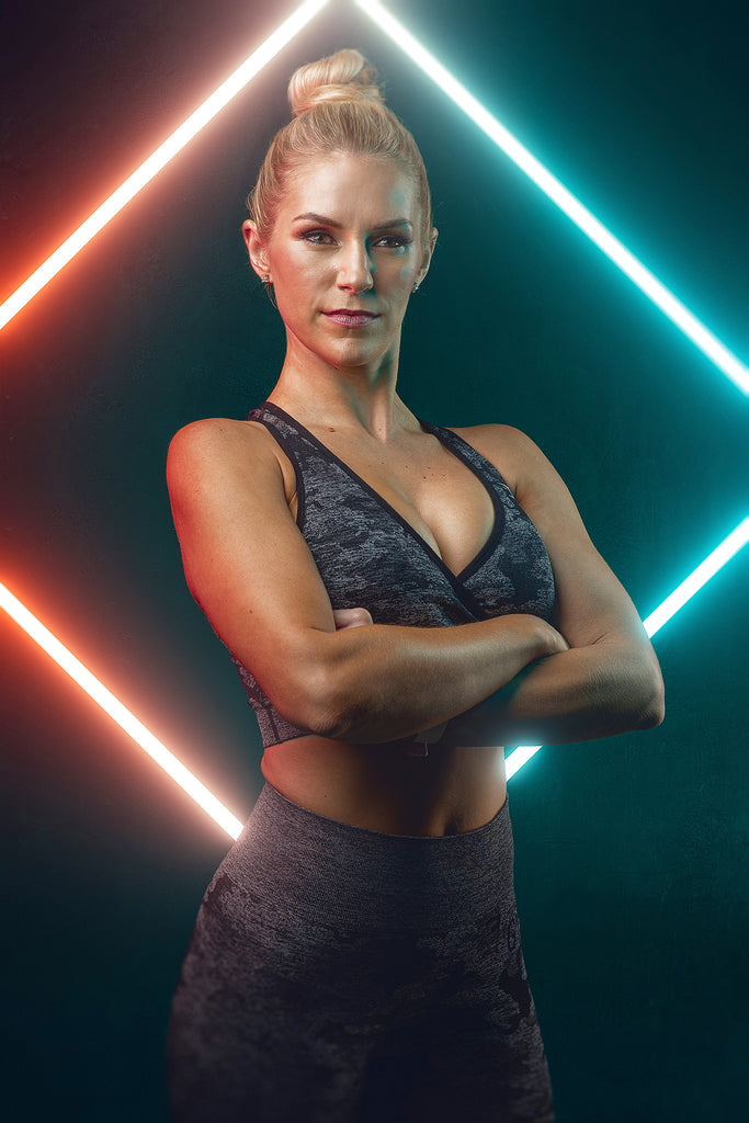 Rich Johnson muscular blond woman arms crossed in front of chest neon lights