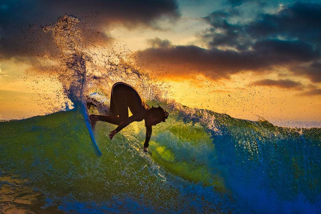 Rick May surfer at sunset silouette green water