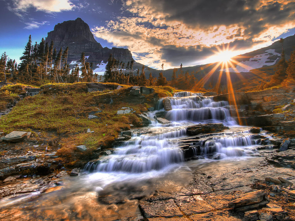 Rick May waterfall cascading down rocks in forest sunset sunrise