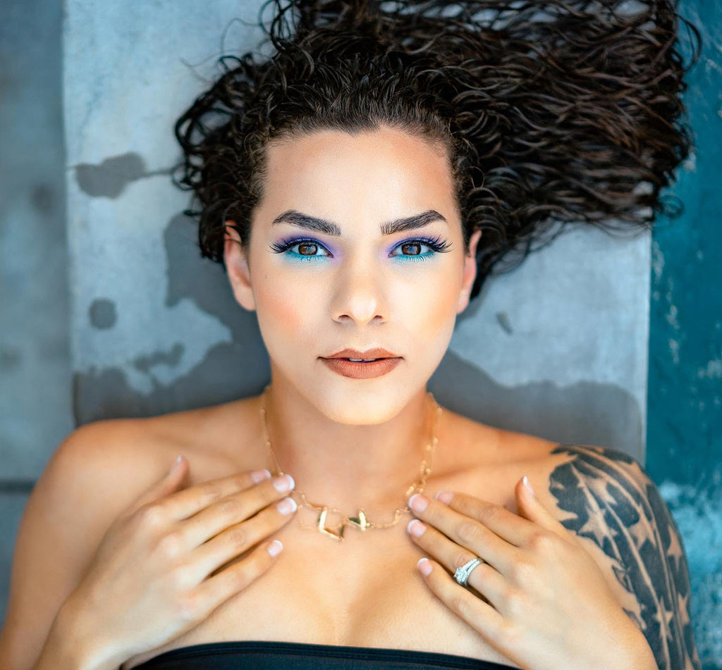 Ron Williams portrait of woman with blue eye makeup hands on chest star feather tatoo on shoulder