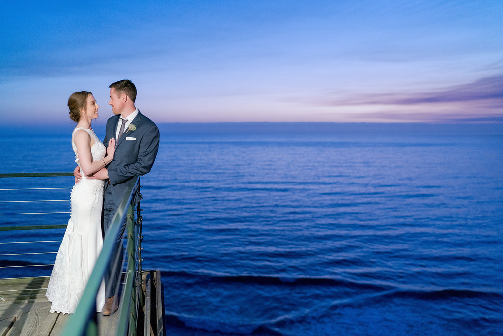 Sara France photograph of bride and groom near water at sunset on pier