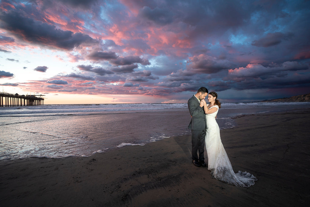 Sara France photograph of bride and groom on beach at sunset pier in background pink puffy skies ocean